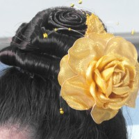 top knot hairdo with yellow rose